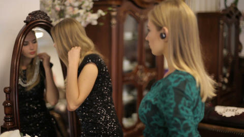 Two beautiful girls choose jewelry in front of a mirror in a chic room ビデオ