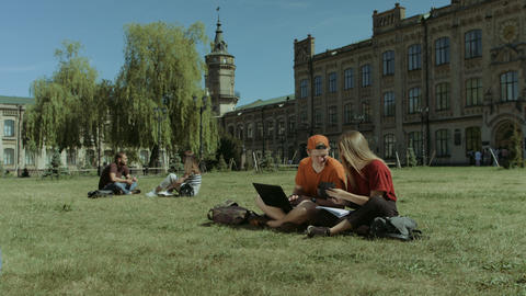 Students with electronic devices studying on lawn Footage