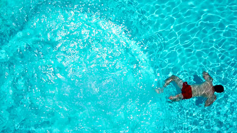 View from the top as a man dives into the pool and swims under the water Footage
