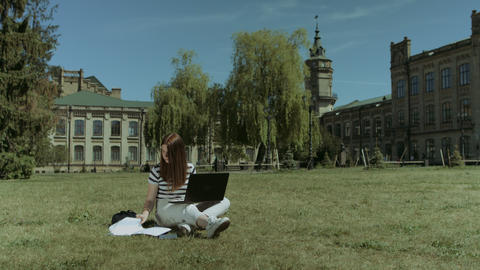 Pretty female student working on laptop on lawn Footage