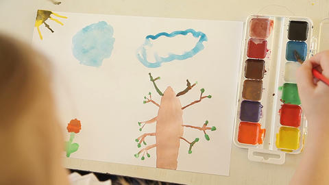The girl paints a blue cloud with a brush and paints Footage