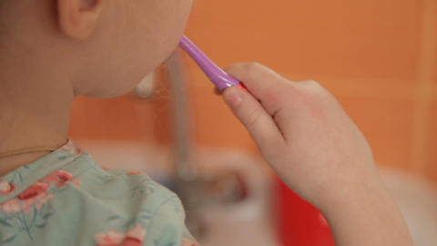 Girl brushing her teeth with a toothbrush Footage