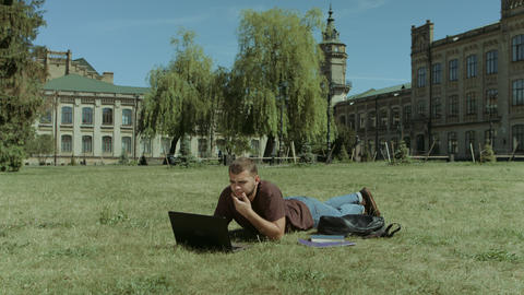 Smart male student working on laptop on campus lawn Footage