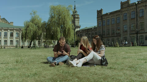 Smiling students networking with smart phones on lawn Footage