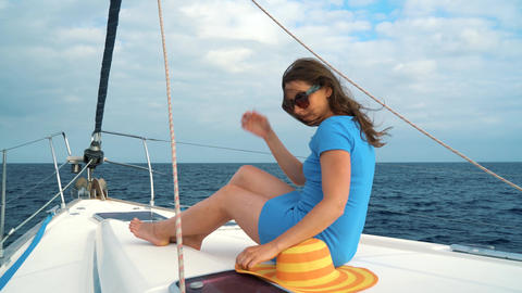 Woman in a yellow hat and blue dress waving hair and smiling on yacht on summer Footage