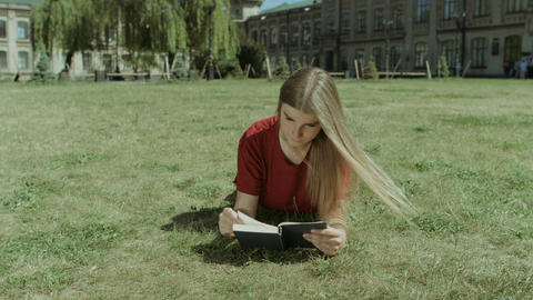 Beautiful girl reading a book on campus lawn Footage