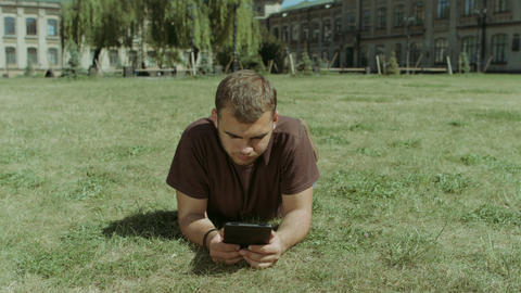 College student working on tablet on campus lawn Footage