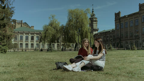 Happy female students relaxing on campus lawn Footage