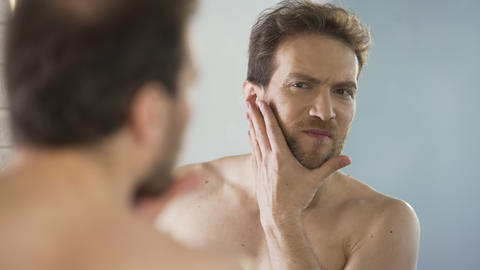 Middle-aged man critically looking at his beard in mirror, morning ritual Footage