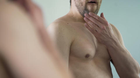Man yawning looking at his mirror reflection, wants to sleep instead of shaving Footage