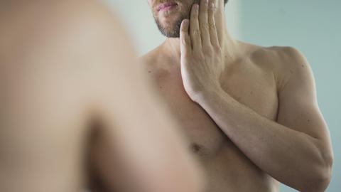 Naked middle-aged man looking in mirror, touching his beard before shaving Footage