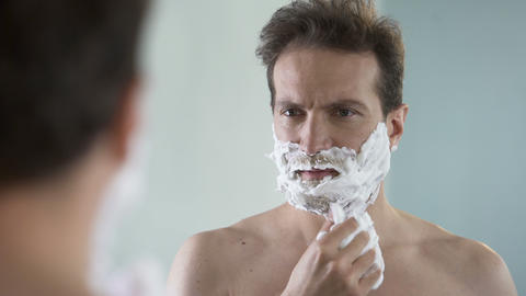 Man preparing to shave, feeling discomfort and tingle on face from shaving foam Footage