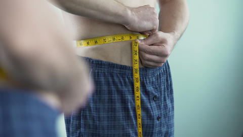 Male with middle-aged crisis measuring his body size, afraid of getting fat Footage