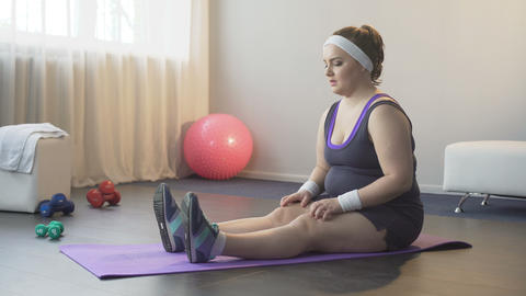 Frustrated fat girl with great difficulty trying to reach toes, stretching Footage