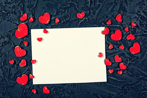 Red hearts and white blank sheet of paper on a black stone background. Valentine Photo