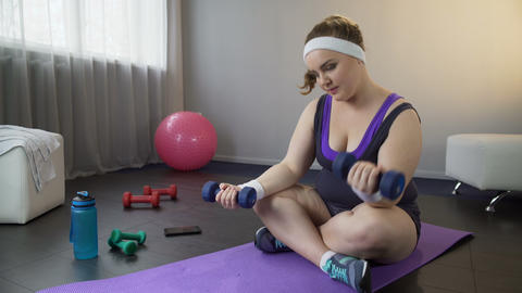 Obese woman easily building up muscles with dumbbells, wants to lose weight Footage