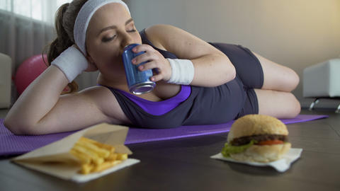 Obese unmotivated lazy girl chewing fastfood, living unhealthy lifestyle Live Action