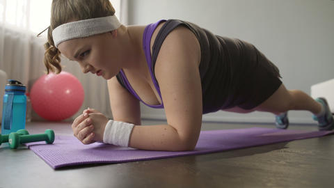 Obese girl gathering strength and spirit, continuing grueling workout at home Footage