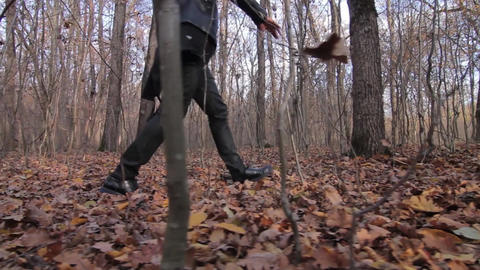 Man dressed in black leather goes through the forest in which the leaves were sh Footage