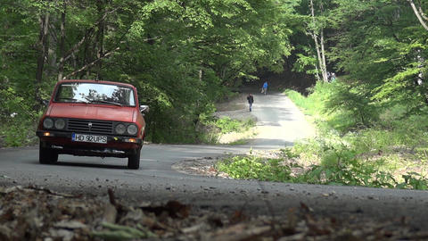 Red car that climbs a slope on the road in the forest, while men are given away  Footage