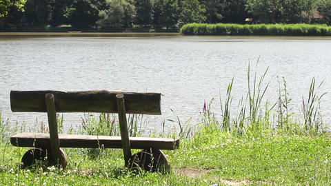 Wooden bench that is at the edge of a lake whose water moves in the wind 89 Footage