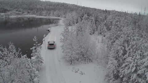 Car getting to winter recreation through pine wood, aerial view Footage