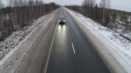 Aerial shot of minivan on winter road Footage