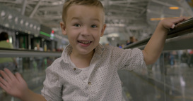 Little child riding on flat escalator and posing Footage