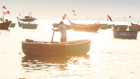 Man Rows Round Vietnamese Fishing Boat among Boats Footage