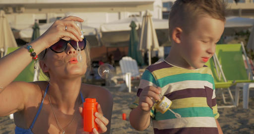 Mother and Son Blowing Soap Bubbles on the Beach Footage