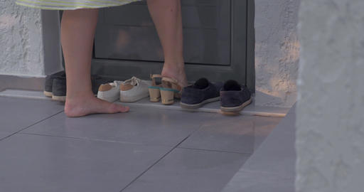 Woman putting on shoes by the house Live Action