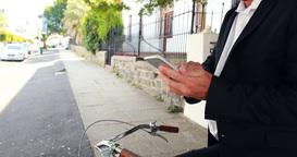 Businessman using smartphone on his bike Footage