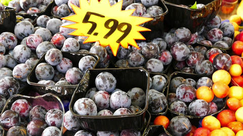 greengrocer and large ripe plums Archivo