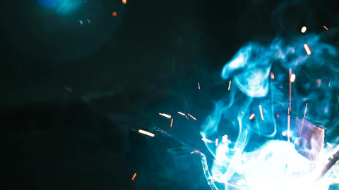 Sparks and smoke from welding metals. Welding of metal structures. Slow motion Live Action