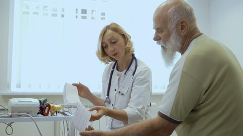 Cardiologist show results of electrocardiography to old patient Live Action