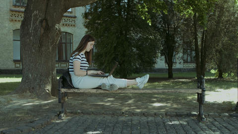 Pretty student with laptop sitting on the bench Footage