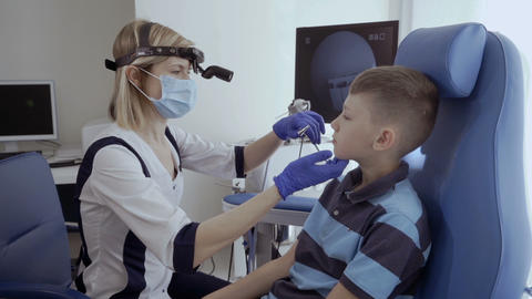 Doctor examine nose of little boy with otoscope Live Action