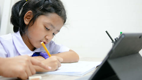 Asian little girl in Thai student uniform doing homework on wooden table select focus shallow depth GIF