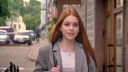 Young charming ginger woman walking in the street and smiling, happy, holding Footage