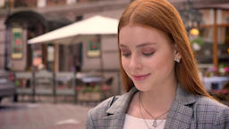 Portrait of young pretty ginger woman standing on city street, looking down and Footage