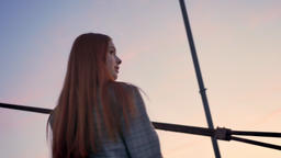 Young beautiful woman with long ginger hair looking in camera and turning around Footage