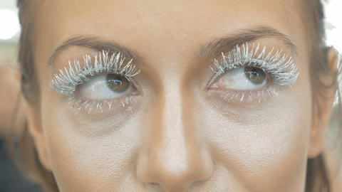 The girl opens her eyes. Big eyelashes, close-up Footage