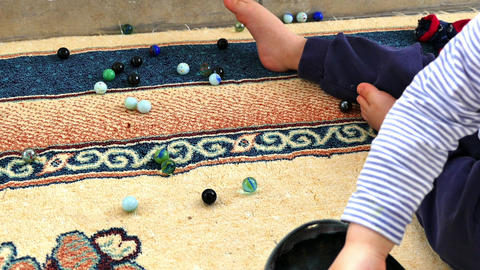A baby playing with glass marbles, colored glass marble, hundreds of colorful Footage