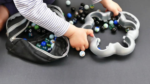 glass marble bag, marble bag on black ground, a baby is playing with glass Footage
