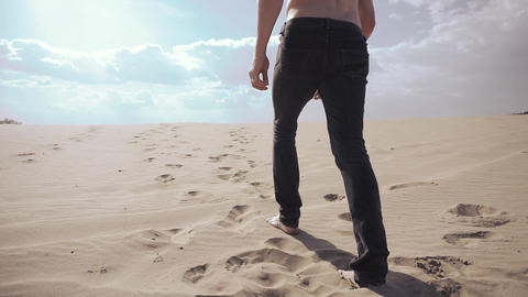 Sexy man is walking along on the sand Live Action