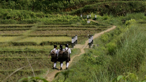 Wide shot of students walking through the village road in Nongpoh,in India GIF