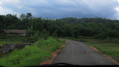 Wide shot of slow-motion of a village road and surrounding hills in Nongpoh GIF