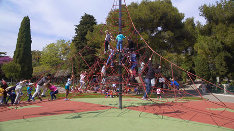Lots of happy kids climbing on cable spider web at children amusement park Footage