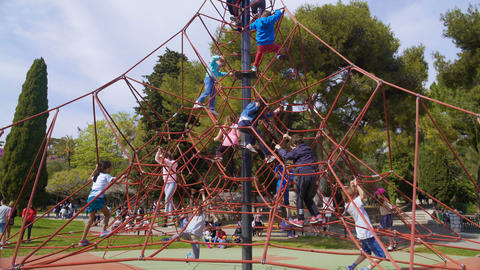 Children competing and climbing on top of large rubber web, amusement park Footage