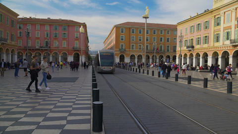 New tram going along square and people crossing road in hurry on their business Footage